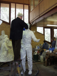 Plowright applying silicone rubber to clay model of Richie Benaud